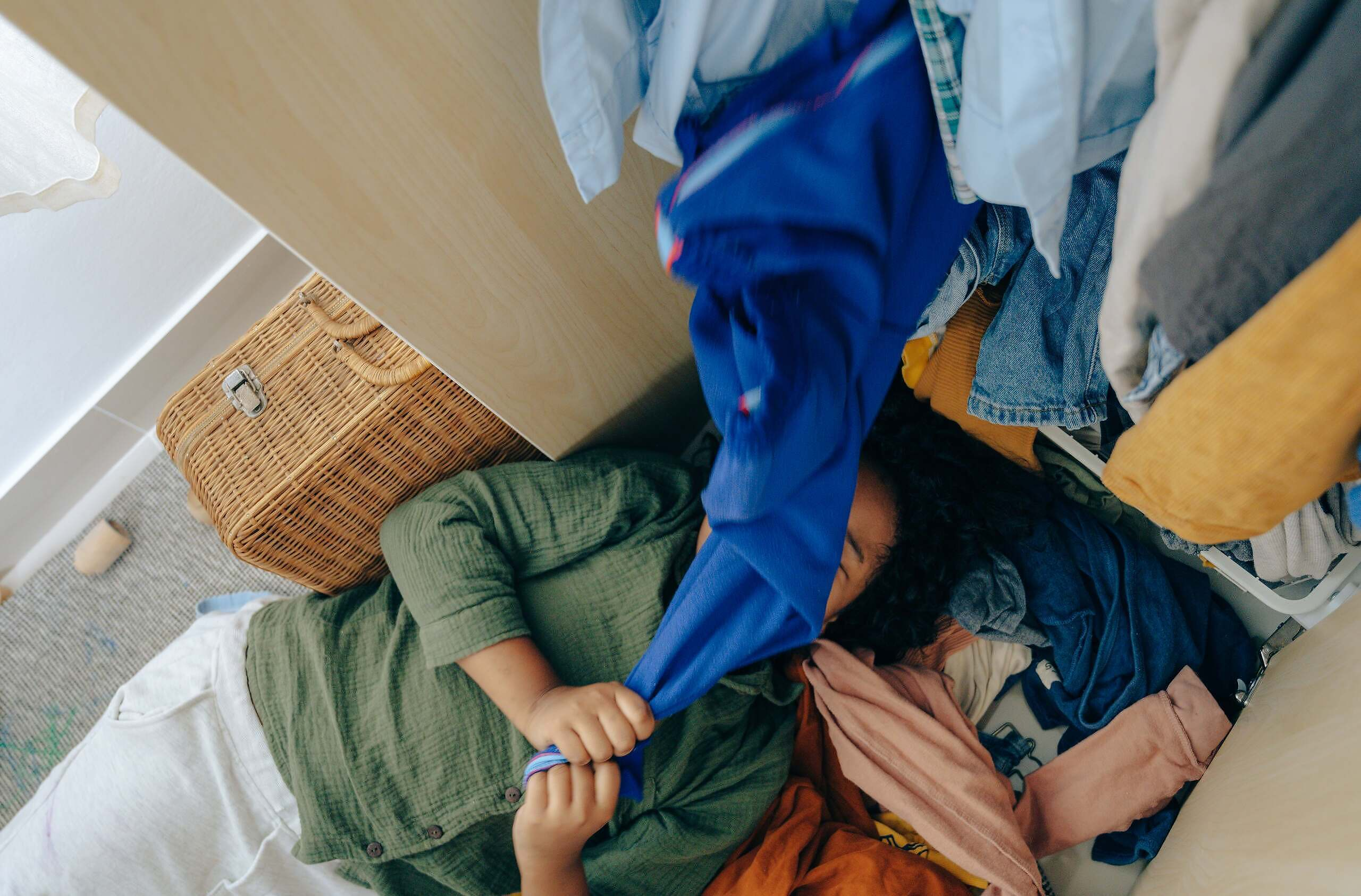 anonymous-black-girl-lying-on-stack-of-clothes-in-bedroom-4545965