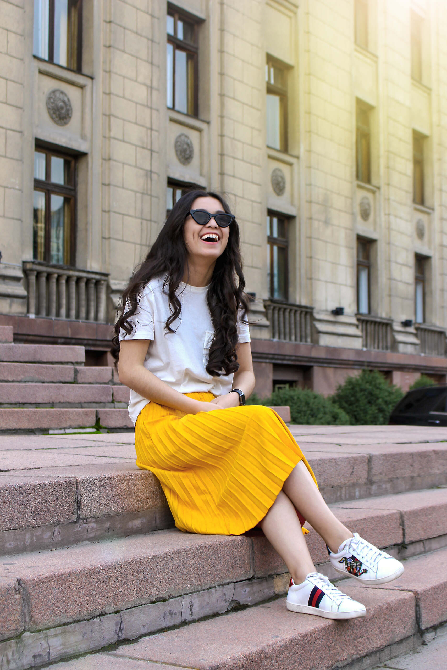 woman-wearing-white-shirt-and-yellow-skirt-sitting-on-brown-983564
